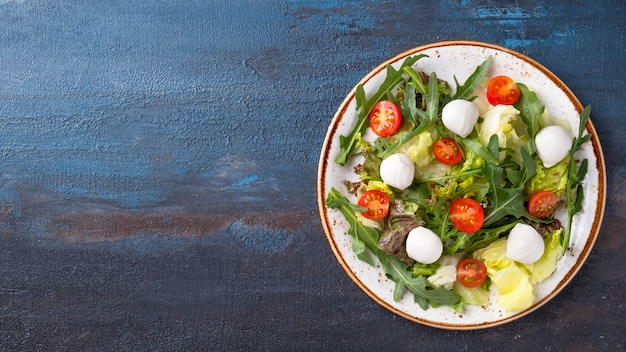 Диетический салат со свежими овощами рукколой и сыром на тарелке
