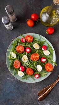 ルッコラ、ウズラeqqs、チェリートマトのダイエットサラダ。皿の上の野菜サラダ。上面図