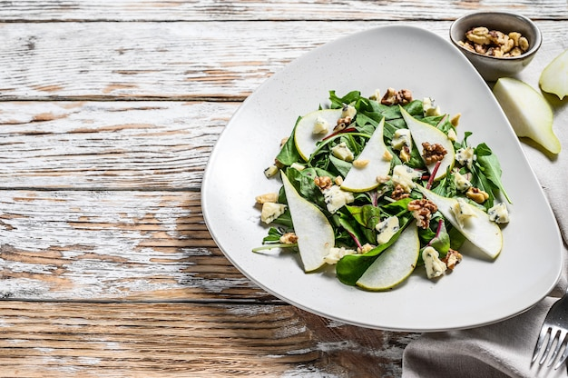 Diet salad with blue gorgonzola cheese, pears, nuts, chard and arugula. white background. top view. copy space.