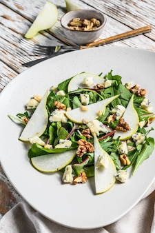 Diet salad with blue gorgonzola cheese, pears, nuts, chard and arugula. white background. top view