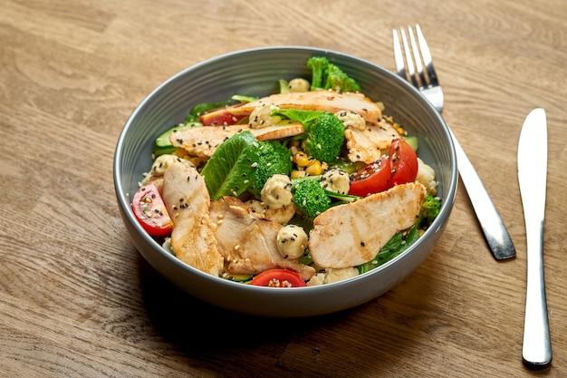 Диетический салат с курицей, брокколи и помидорами черри в миске на деревянном фоне. крупным планом, выборочный фокус