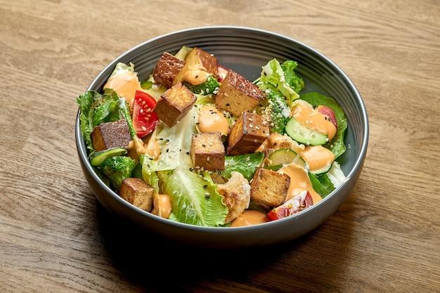 Диетический салат с жареным тофу, желтым соусом и овощами в миске на деревянном фоне