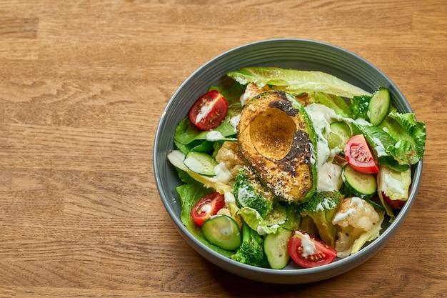 Диетический салат с авокадо гриль, белым соусом и овощами в миске на деревянном фоне с шумовым зерном