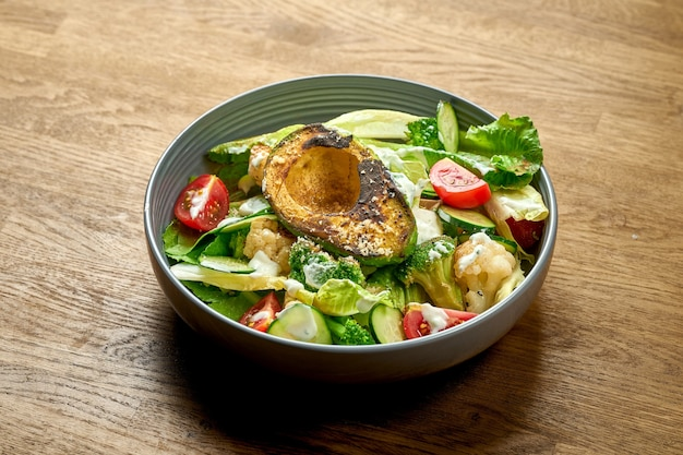 Диетический салат с авокадо гриль, белым соусом и овощами в миске на деревянном фоне