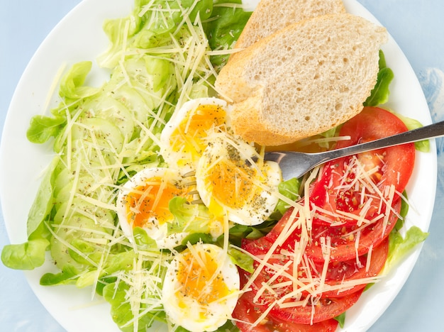 Diet salad with soft boiled eggs, cheese and vegetables - tomatoes, lettuce.