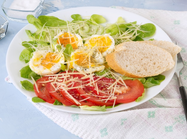 Diet salad with soft boiled eggs, grated cheese and vegetables - tomatoes, lettuce.