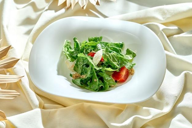 Диетический салат с помидорами и киноа в белой тарелке на скатерти