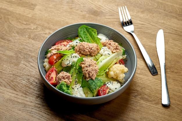 Диетический салат с тунцом, брокколи и помидорами черри в миске на деревянном фоне
