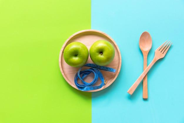 Диета для похудения вес с зеленым яблоком и измерительный кран на деревянной тарелке, красочный фон. диета и здоровая концепция