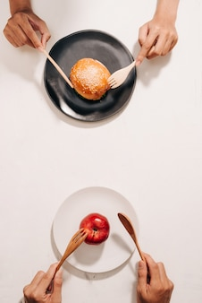 다이어트 투쟁과 건강에 좋은 신선한 과일과 채소 또는 콜레스테롤이 풍부한 패스트 푸드 사이에서 영양 선택 딜레마 사이에서 결정 손 케이크와 사과 선택 무엇을 먹을지 결정하기 위해 경쟁