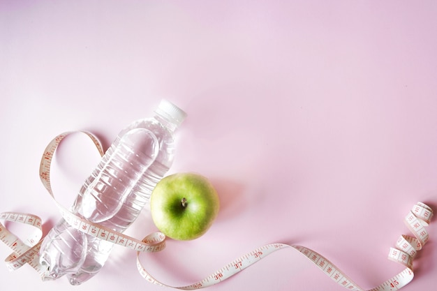 Diet symbol flat lay one meter ribbon and green apple and a bottle of water