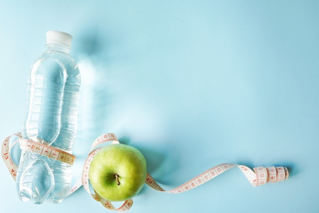 Diet symbol flat lay one meter ribbon and green apple and bottle of water.