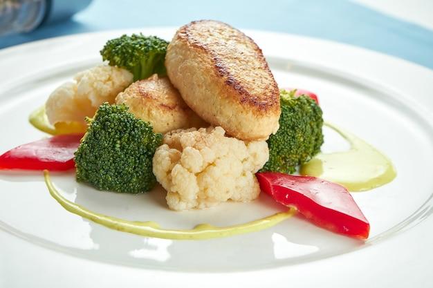 Диетические котлеты из индейки, украшенные тушеными овощами в белой тарелке на синей скатерти.
