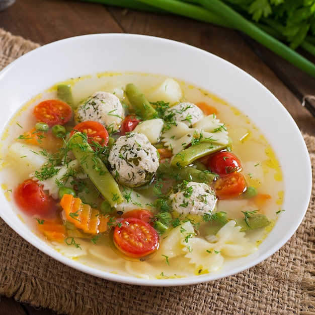 Diet vegetable soup with chicken meatballs and fresh herbs in wooden bowl