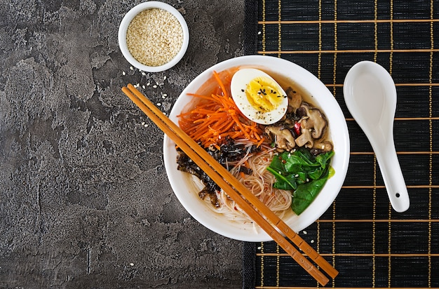Diet vegetarian bowl of noodle soup of shiitake mushrooms, carrot and boiled eggs.  japanese food. top view. flat lay