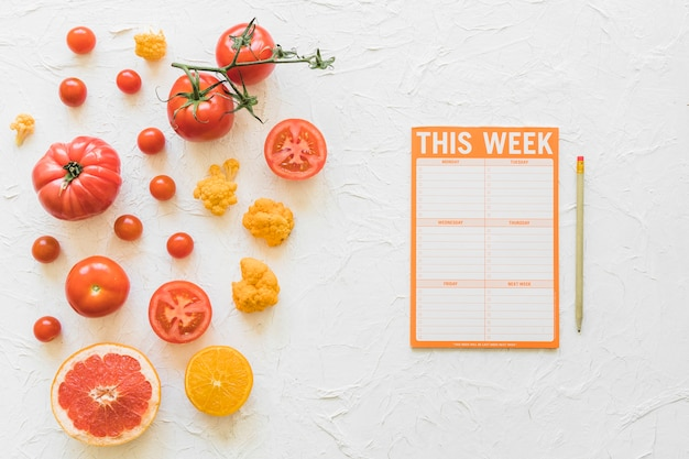 Diet week paper with pencil and healthy vegetables on white background