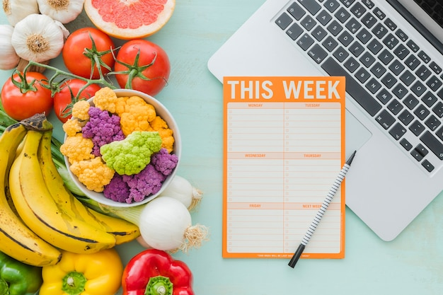 Diet week plan and healthy vegetables on background