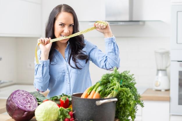 Концепция потери веса и здоровья диеты - красивая молодая женщина со свежими овощами и измерительной лентой на ее кухне.