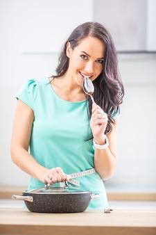 Концепция потери веса и здоровья диеты - красивая молодая женщина с рулеткой на ее кухне.