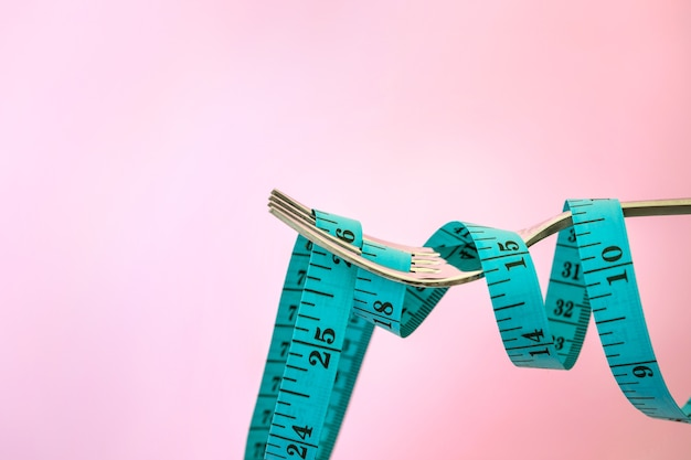 Diet for weight loss , measuring tape with fork on a light pink background