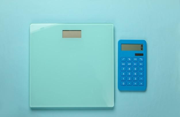 Диета, похудание, натюрморт. подсчет калорий. калькулятор и весы на синем. минимализм. плоская планировка
