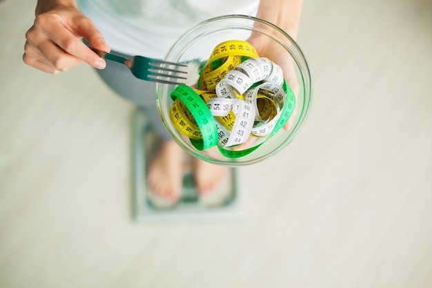 Diet and weight loss. woman holds bowl and fork with measuring tape.