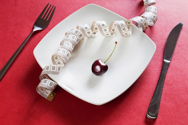 Диета белая тарелка с сантиметром, вишня, вилка и нож