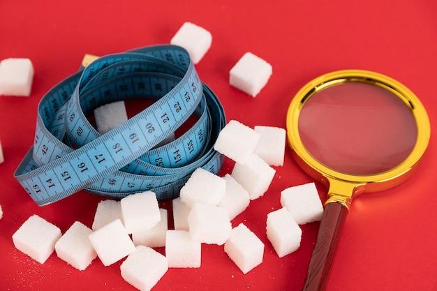減量のための砂糖なしの食事療法。白い角砂糖の山とその中に青い巻尺。赤い背景。スペースをコピーします。