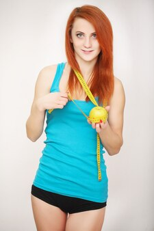 Diet, woman holding a green apple and measuring