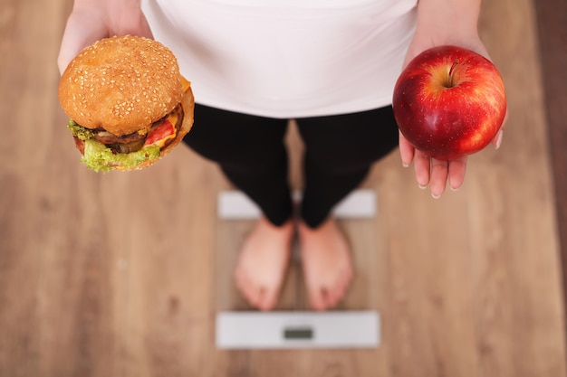 Diet, woman measuring body weight on weighing scale holding burger and apple
