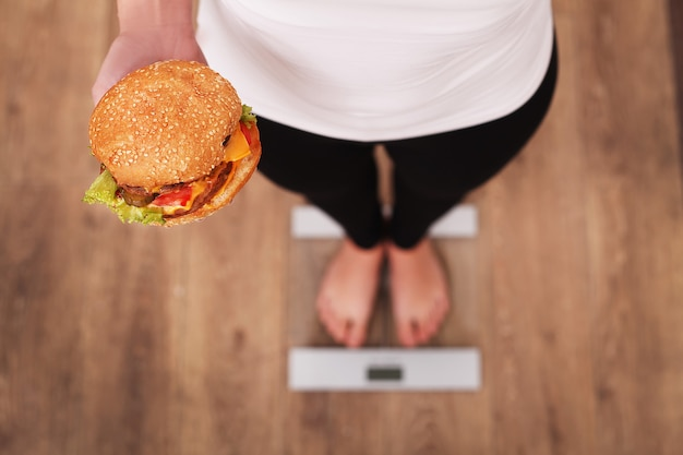 Diet. woman measuring body weight on weighing scale holding burger and apple.