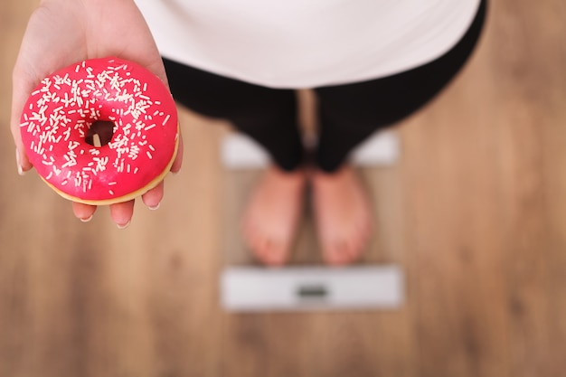 Diet, woman measuring body weight on weighing scale holding donut