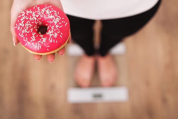 Diet. woman measuring body weight on weighing scale holding donut.