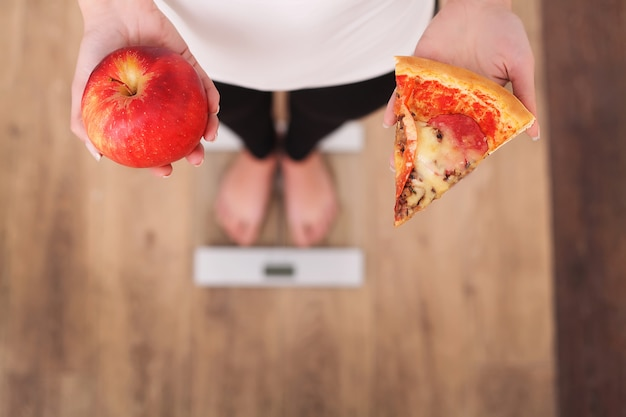 Diet. woman measuring body weight on weighing scale holding pizza.