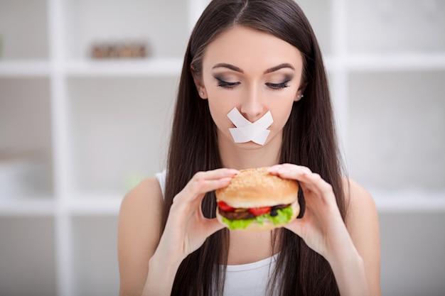 ダイエット。女性はジャンクフードを食べることを拒否します。健康的な食事とアクティブなライフスタイル