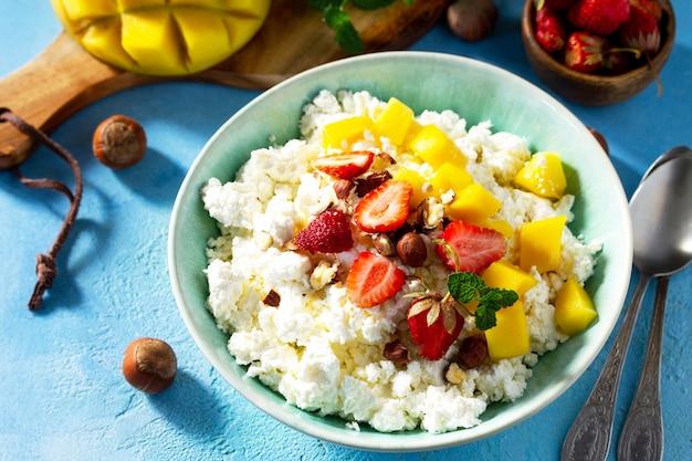 여름을 위한 식이 아침 식사 딸기 망고와 견과류를 곁들인 신선한 코티지 치즈