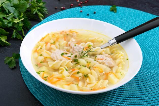 Диетический куриный суп с фузилли в белой миске на черном фоне