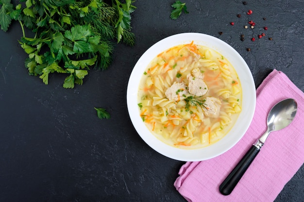 Dietary chicken soup with fusilli in a white bowl on a black background. the top view.