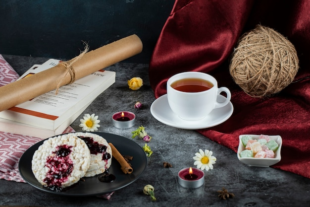Dietary crackers with red jam and cinnamon and a cup of tea