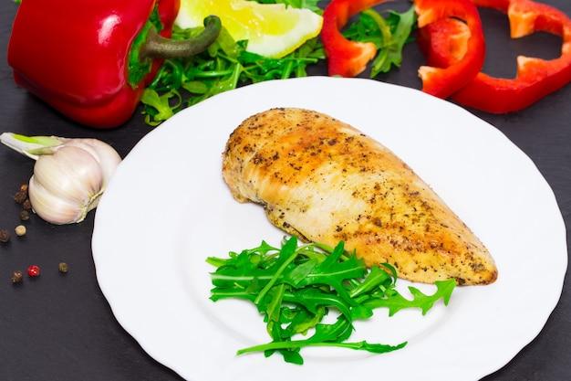 Диетическая кухня - куриная грудка на гриле с листьями рукколы и овощами на темном фоне.