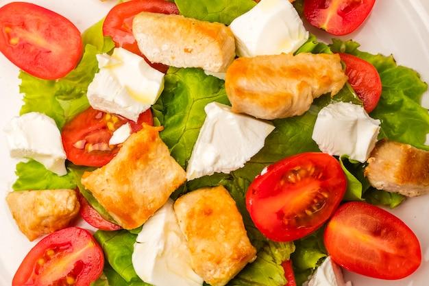 ダイエット料理。チキン、チェリートマト、ソフトチーズチーズのサラダ。オリーブオイルのドレッシング。閉じる