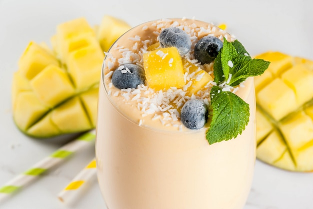 Dietary drink, breakfast. tropical mango smoothie with fresh pieces of mango, blueberries, coconut and mint leaves. in a glass jar, on a white marble table. copyspace close view