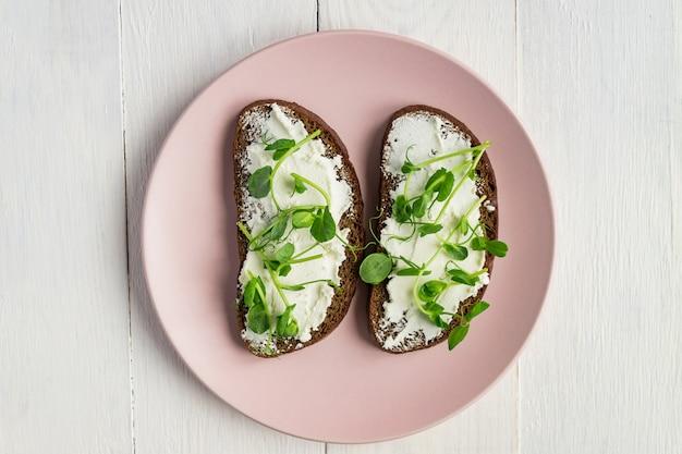Диетические фитнес тост с ростками сливочного сыра и гороха на белом, вид сверху.