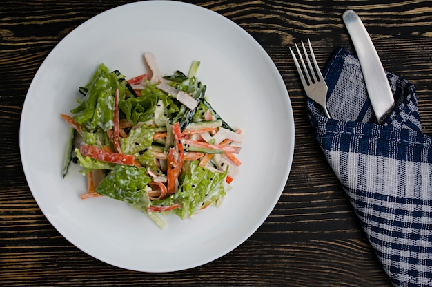 Dietary food, fresh vegetable salad with imitation of crab stick, pieces of meat, dressed with sour cream and japanese sesame