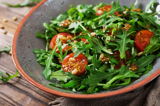Dietary menu. vegan cuisine. healthy salad with arugula, tomatoes and pine nuts.