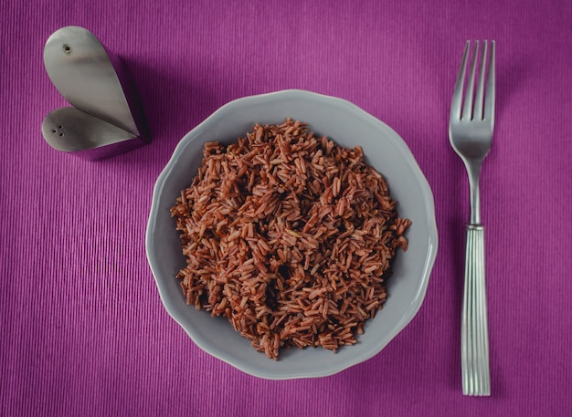 Dietary proper nutrition. a plate of brown rice on a beautiful purple table