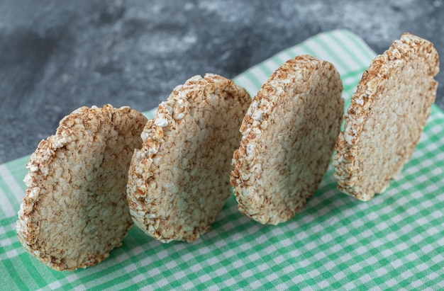 Dietary round rice cakes on striped tablecloth.