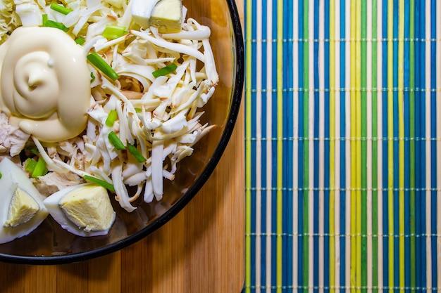 緑のマットの上に鶏肉と卵を入れた適切な栄養のためのダイエットサラダ。