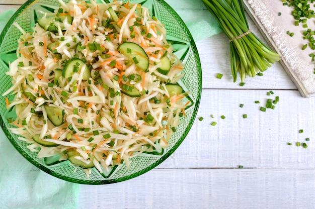 Диетический салат с капустой, огурцом, морковью, зеленью. сочный весенний салат из свежих овощей на белом фоне деревянные. правильное питание. вид сверху