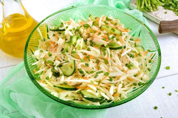 Диетический салат с капустой, огурцом, морковью, зеленью. сочный весенний салат из свежих овощей на белом фоне деревянные. правильное питание.